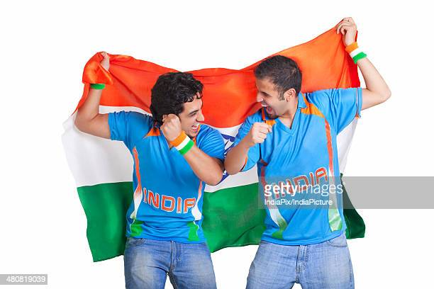 Excited young male friends in jerseys cheering while holding Indian flag over white background