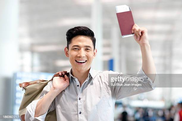 Excited young man at the airport with flight ticket and passport
