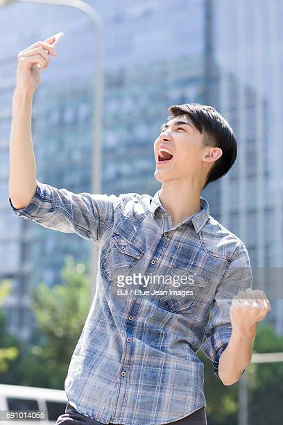 Excited young man holding a smart phone