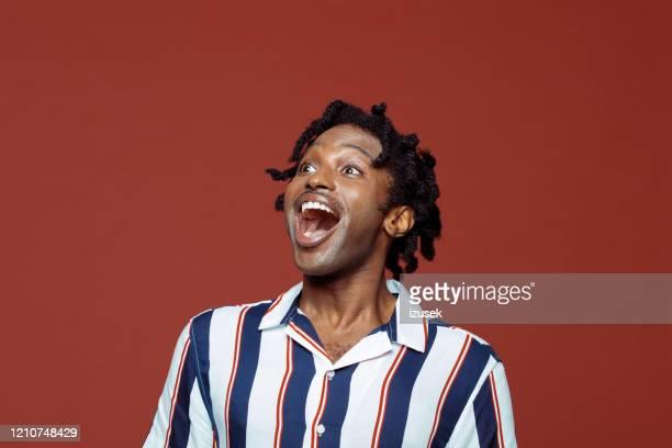 jeune homme excité dans le modèle rétro rayé chemise à manches courtes - en manches courtes photos et images de collection