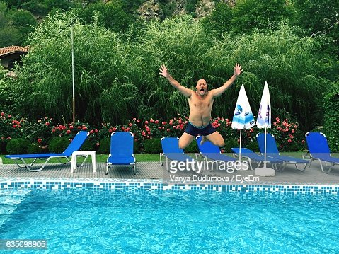 Excited Young Man Jumping In Swimming Pool