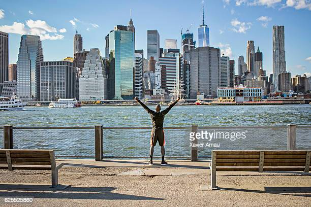 Excited young man on promenade with Manhattan skyline