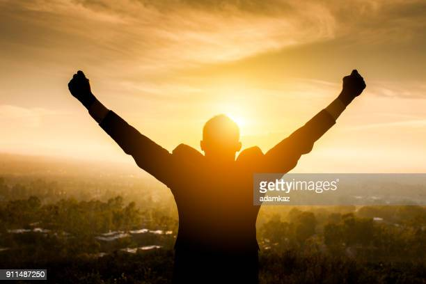 Excited Young Man Raising Arms
