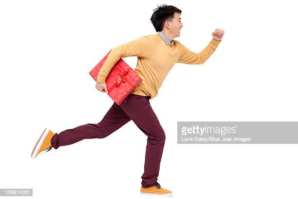 Excited young man running with gift in Chinese New Year
