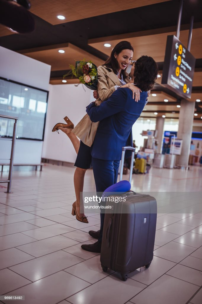 Excited young man welcoming girlfriend with flowers at airport : Stock Photo