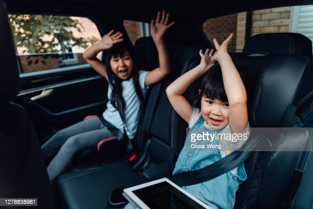 excited young sisters waving hands in the car - singing stock pictures, royalty-free photos & images