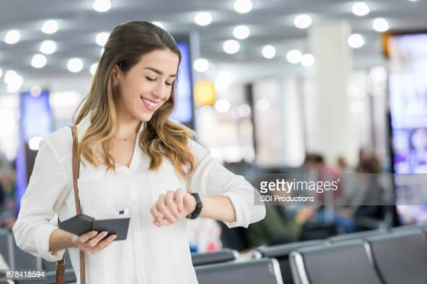 Excited young woman checks time at airport terminal gate