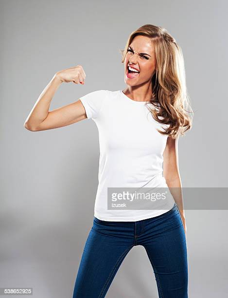excited young woman flexing her bicep, studio portrait - flexing muscles stock pictures, royalty-free photos & images