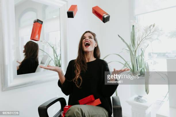 excited young woman juggling with cosmetics in beauty salon - 投げる ストックフォトと画像