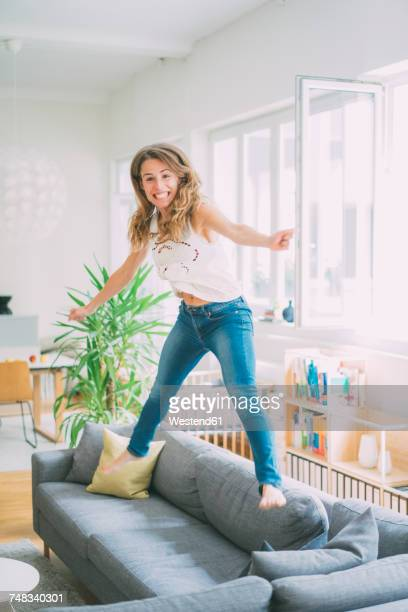 Excited young woman jumping on couch at home