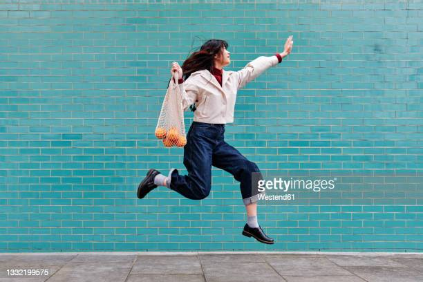 excited young woman jumping while holding mesh bag by turquoise brick wall - mid air stock pictures, royalty-free photos & images