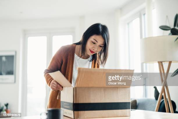 excited young woman opening a delivery box at home - open stock pictures, royalty-free photos & images