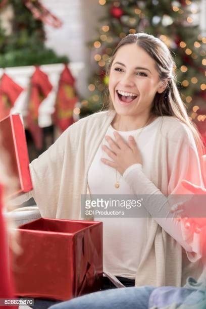 Excited young woman opens Christmas present