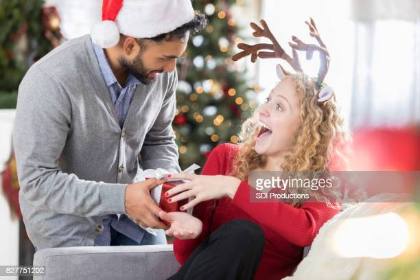Excited young woman receives Christmas gift from husband