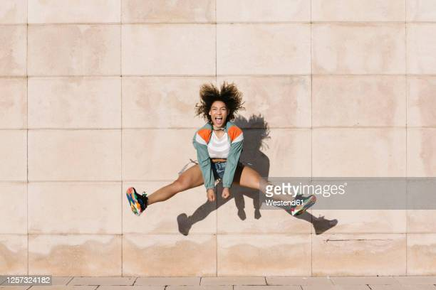 excited young woman screaming while jumping against wall during sunny day - hochspringen stock-fotos und bilder