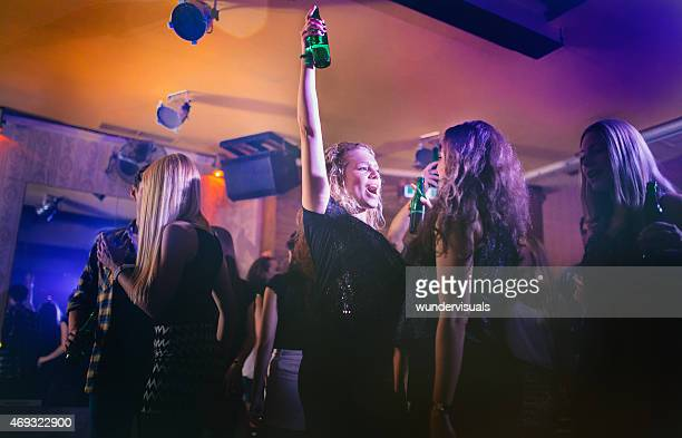 Excited young woman shouting happily at a party
