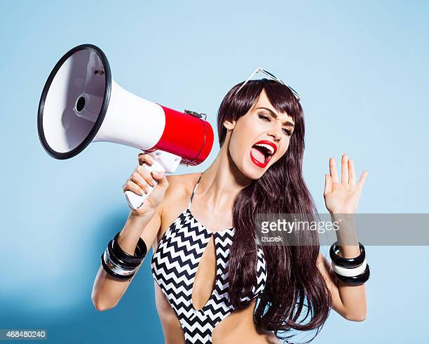Excited young woman wearing swimsuit screaming into magaphone