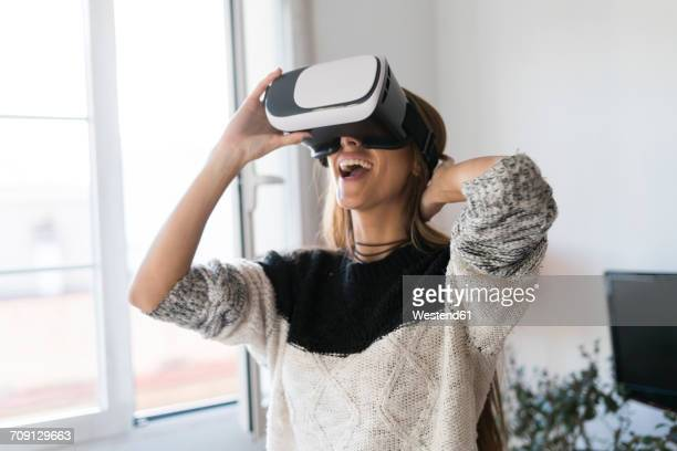 excited young woman wearing vr glasses at home - simulatore di realtà virtuale foto e immagini stock