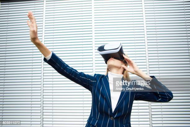 excited young woman wearing vr glasses near office - digital native stock-fotos und bilder