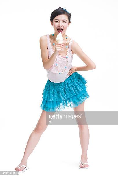 Excited young woman with ice cream cone singing