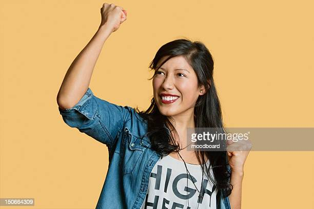 Excited young woman with raised fist while looking away over colored background