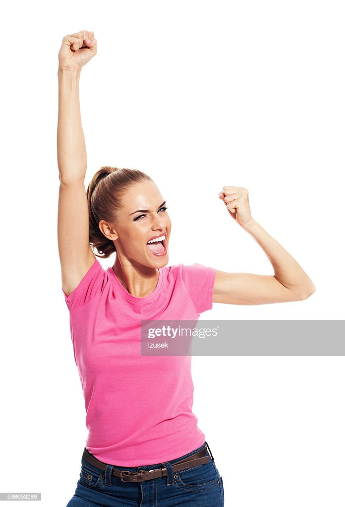 Excited young woman with raised fists, Studio Portrait : Stock Photo