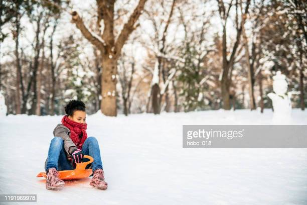 exciting tobogganing down the snow hill - tobogganing stock pictures, royalty-free photos & images