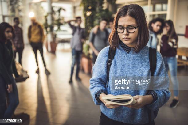 excluded high school student reading a book in a hallway. - exclusion stock pictures, royalty-free photos & images
