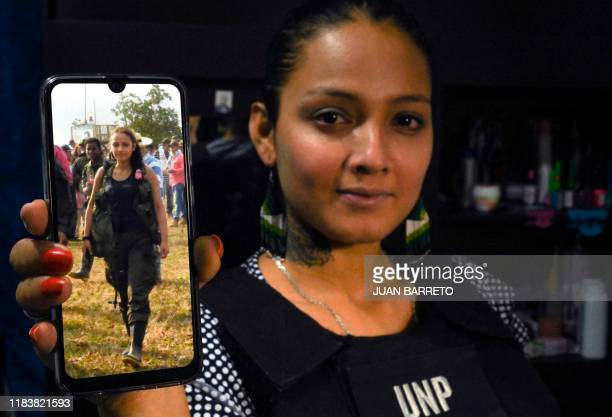 EP excombatant Alexandra Fontecha shows her mobile phone with a picture of her of when she was part of the FARC during an interview in Bogota on...