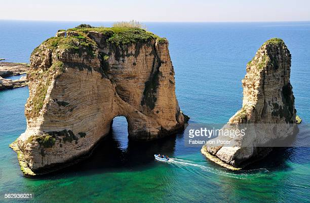Excursion boat off the Pigeons Rock, Grotte aux Pigeons, limestone rocks eroded by wind and weather in the Raouche district, Beirut, Lebanon, Middle East, Asia