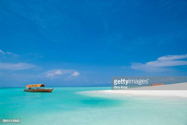 excursion boat tied up by a sandy beach - zanzibar photos et images de collection