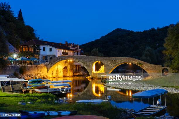 excursion boats and old bridge stari most at dusk, river crnojevic, rijeka crnojevica, national park lake skadar, province cetinje, montenegro - montenegro imagens e fotografias de stock