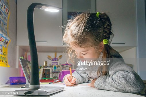 Execution of school lessons late in the evening by the light of a table lamp.
