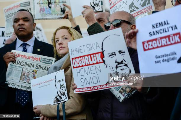 Executive Board Chairman International Press Institute John Yearwood PEN International Policy and Advocacy Manager Sarah Clarke and protesters hold...