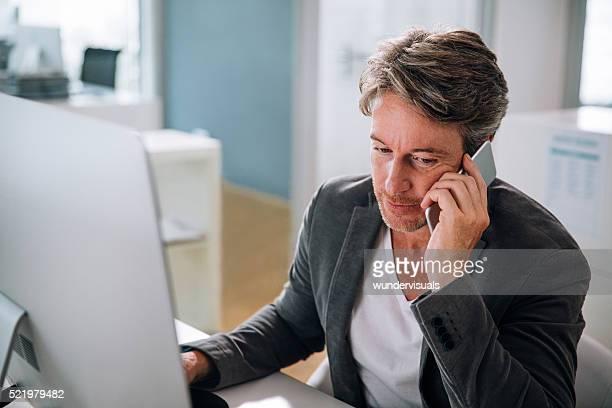 エグゼクティブのビジネスの男性が会話をスマートフォン