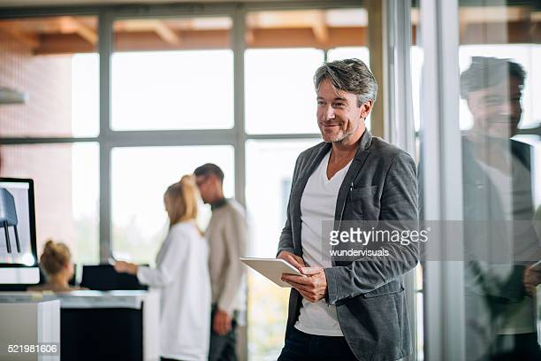 Executive businessman leaning against window holding tablet.