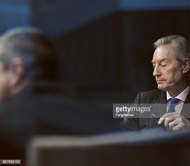 Executive businessman looking at notes in meeting