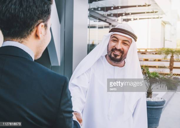 executive businessman shaking hands with a arab businessman outdoor - community work stock pictures, royalty-free photos & images