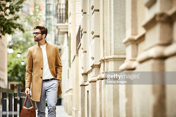 executive carrying bag with hand in pocket at city - smart casual stock pictures, royalty-free photos & images