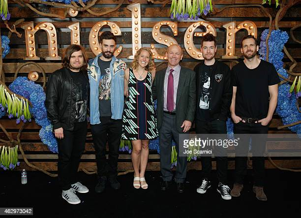 Executive Chairman of Nielsen Dave Calhoun and wife Amy Calhoun with Chris Wood Kyle Simmons Dan Smith and Will Farquarson of Bastille attend Nielsen...