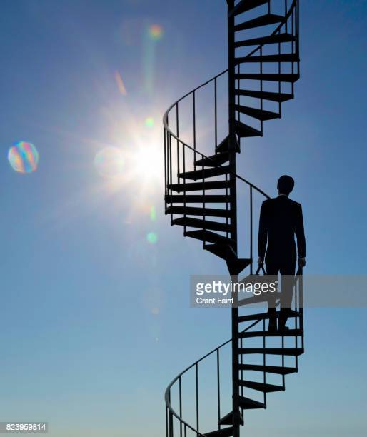 Executive climbing spiral steps.