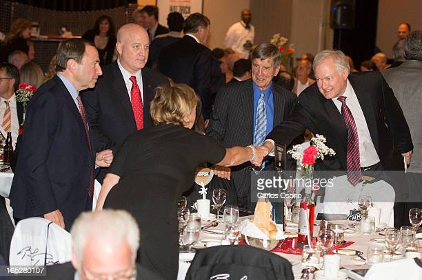 NHLPA executive director Donald Fehr shakes hands with Janet Hull during the NHL Alumni dinner on September 24 2012 Sitting at the same table are NHL...