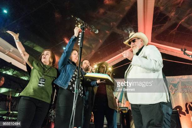 Executive director of HAAM Reenie Collins presents lead guitarist and vocalist Ray Benson of Asleep At The Wheel with a birthday present live on...
