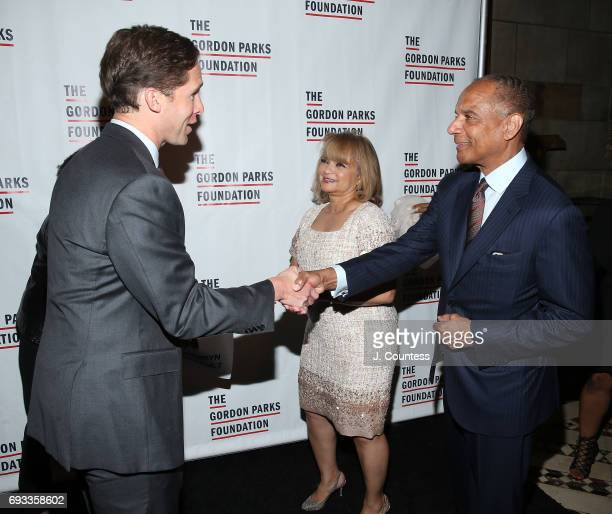 Executive Director of the Gordon Parks Foundation Peter Kunhardt Jr greets CEO of American Express Kenneth Chenault and Kathryn Chenault during the...