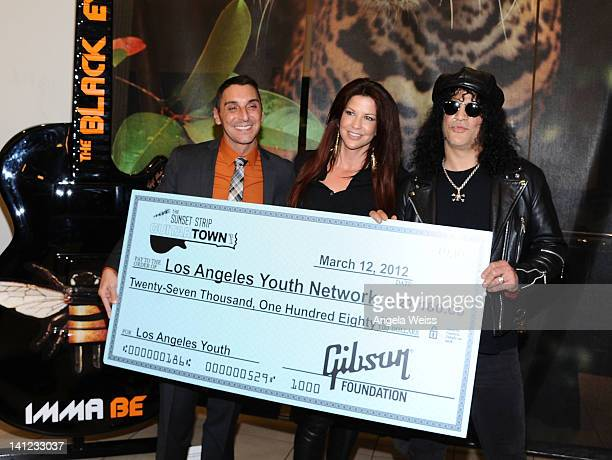 Executive director of the Los Angeles Youth Network Mark Supper Perla Hudson and musician Slash attend the unveiling of the 2012 Gibson Guitartown...