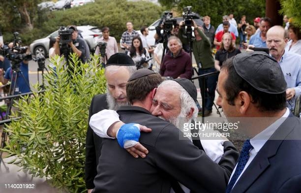 Executive Director Rabbi Yisroel Goldstein who was shot in the hands hugs his congregants after a press conference outside the Chabad of Poway...