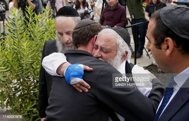 Executive Director Rabbi Ysrael Goldstein who was shot in the hands hugs his congregants after a press conference outside the Chabad of Poway...
