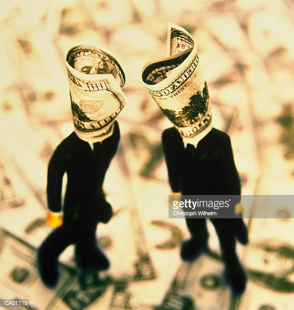 Executive figurines standing on money, elevated view