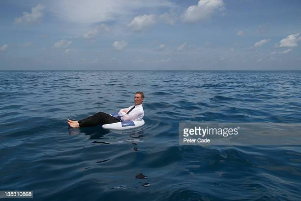 executive floating drifting in sea in rubber ring