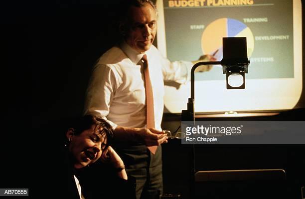 executive giving presentation, woman yawning - overheadprojector stockfoto's en -beelden